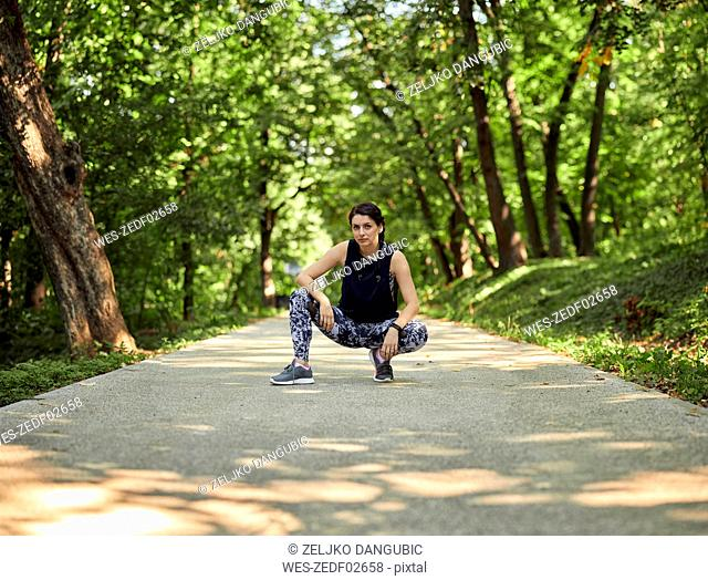 Portrait of sporty young woman crouching on forest path