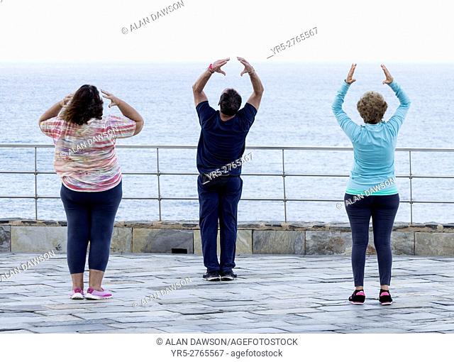 Mature man and two mature women practicing tai chi overlooking the Atlantic Ocean in Las Palmas, the capital of Gran Canaria, Canary Islands, Spain