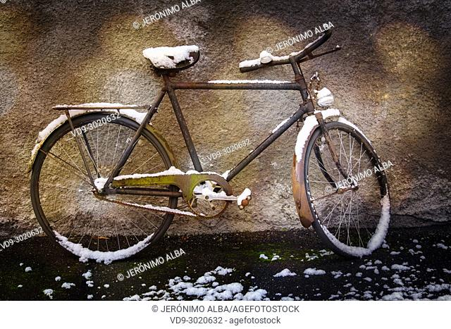 Old forgotten bicycle under the snow on a wall, snow scene. Troinex, Geneva. Switzerland; Europe