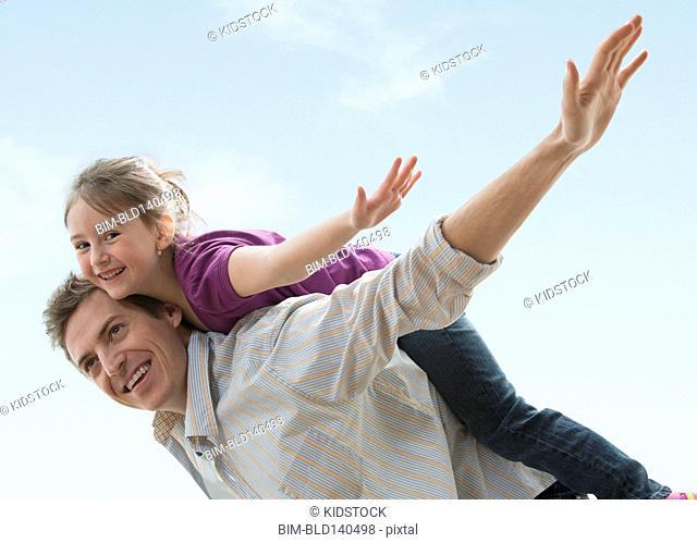 Caucasian father carrying daughter piggyback outdoors