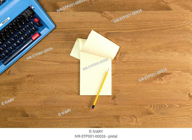 High Angle View Of The Notepad And The Typewriter At The Corner