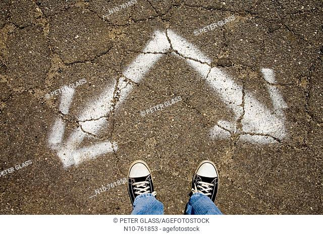 Close-up of a man's feet standing next to two arrows painted on a driveway