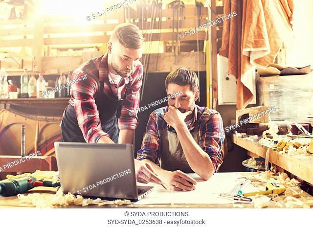 carpenters with laptop and blueprint at workshop