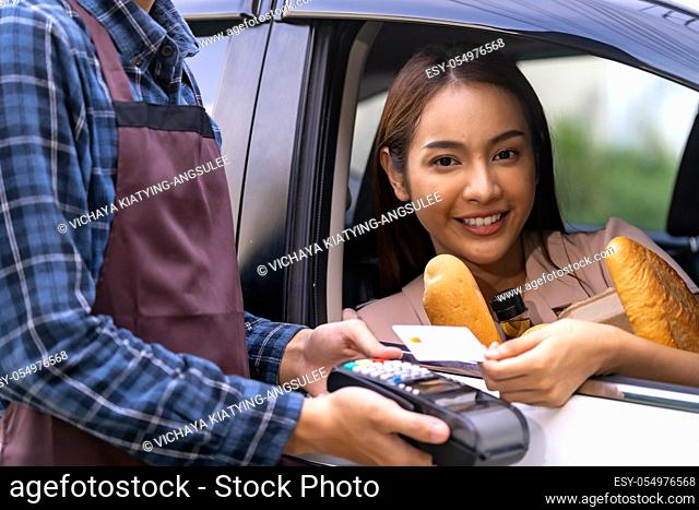 Portrait of asian woman make mobile payment contactless technology for online grocery ordering and drive thru service. Drive through and food online is new...