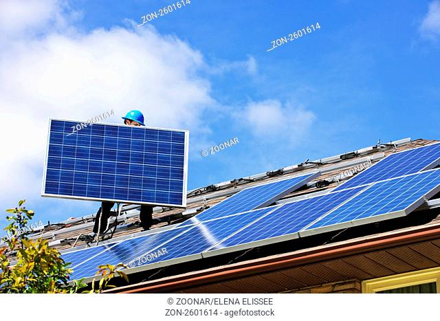Worker installing alternative energy photovoltaic solar panels on roof