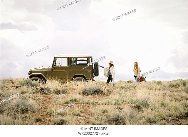 Two women by a jeep in open space, loading up for a road trip