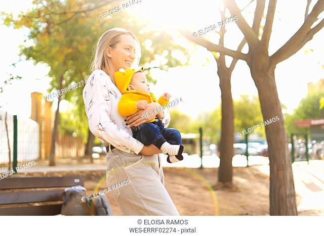 Happy mother carrying baby boy in a park