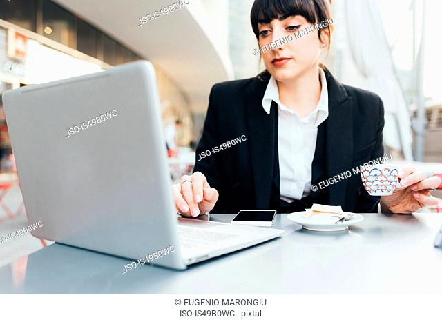 Businesswoman using laptop in coffee shop, Milan, Italy