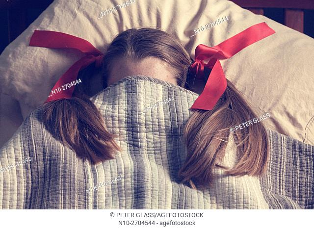 Teenage girl, wirh red ribbons holding her pigtails, lying in bed
