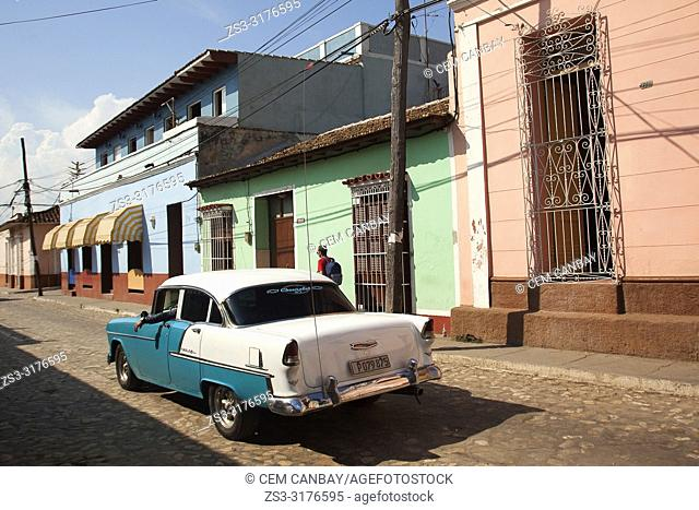 Old American car used as taxi in front of colonial houses in the city center, Trinidad, Sancti Spiritu Province, Cuba, West Indies, Central America
