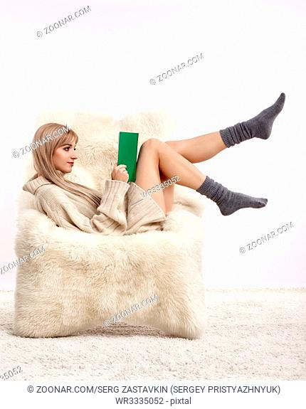 Portrait of beautiful blonde woman with book in hands. Female is dressed in white cashmere sweater and woolen socks. Girl is sitting on white fur arm-chair...