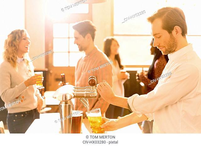 Bartender pouring beer at beer tap behind bar