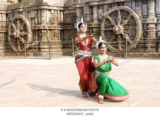 Dancers performing classical traditional odissi dance in front of Konarak Sun temple , Konarak , Orissa , India MR 736C,736D