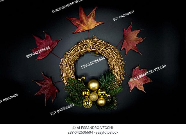 Holidays wallpaper background of twig Christmas wreath with golden balls and decorations, green branches and red dried leaves on black background