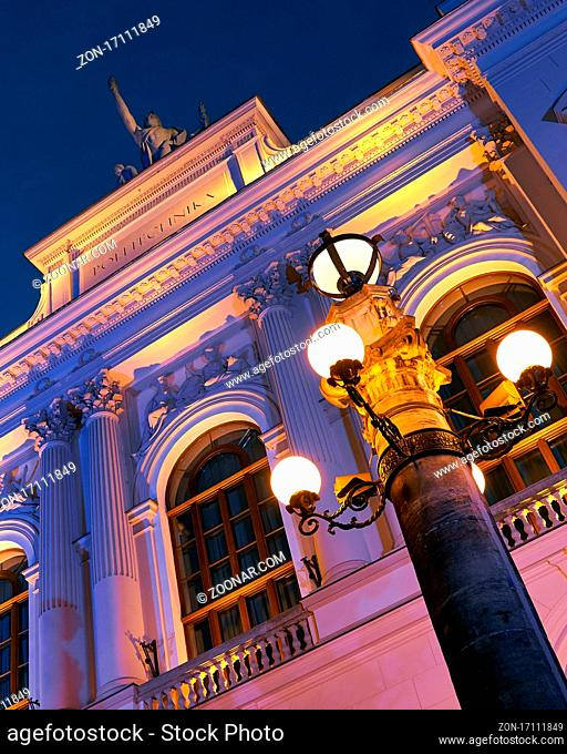 Facade of the main building of Warsaw University of Technology in the evening lit by colorful lights. Warsaw, Poland