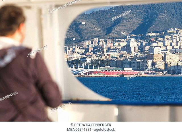 A man looks over the Mediterranean Sea up to the harbour of Genoa, Italy