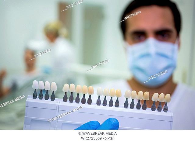 Dentist holding teeth shades