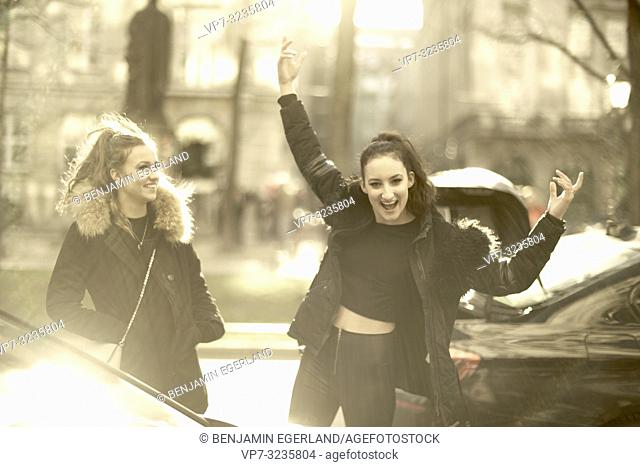 Two young vibrant sisters at street in city, wearing winter clothing, Munich, Germany