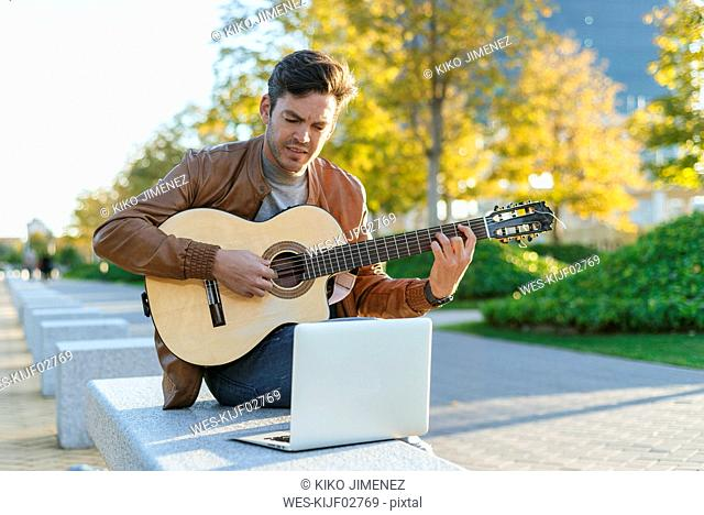 Man with laptop playing guitar in the city, Madrid, Spain