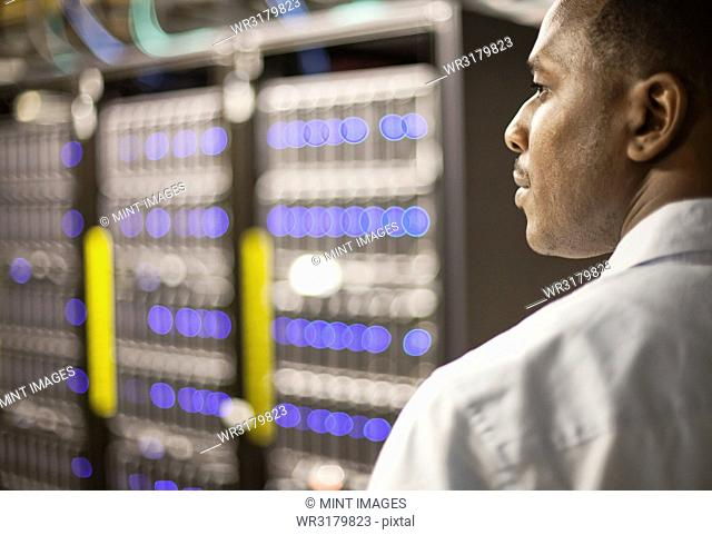 Black man technician doing diagnostic tests on computer servers in server farm