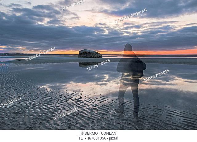 USA, Massachusetts, Cape Cod, Orleans, Ghostly figure on beach at dusk