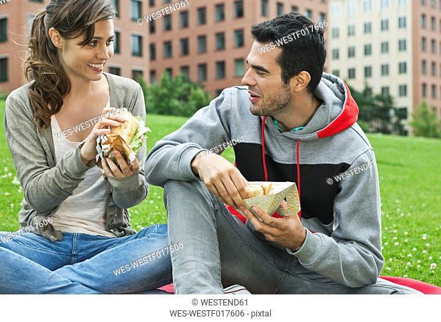 Germany, Berlin, Couple eating food in park