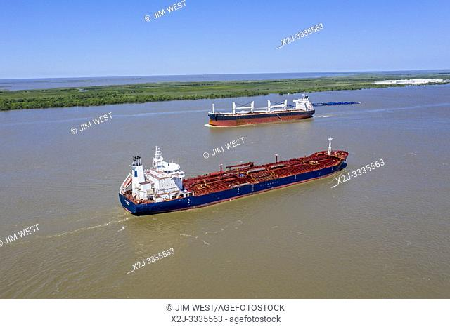Empire, Louisiana - Ships on the Mississippi River below New Orleans. The Liberian oil/chemical tanker Tintomara (foreground) sails towards the Gulf of Mexico