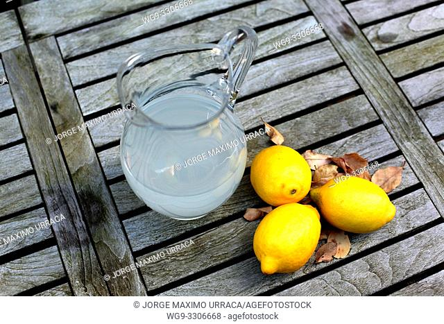 Lemon juice and lemons on a wooden table