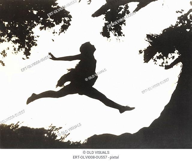 Silhouette of a woman in mid-air jumping between two trees