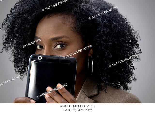 Businesswoman hiding behind digital tablet