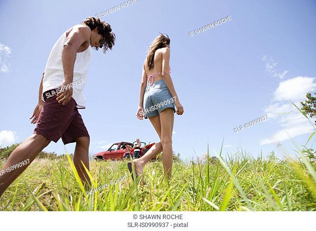 Young couple walking through grass
