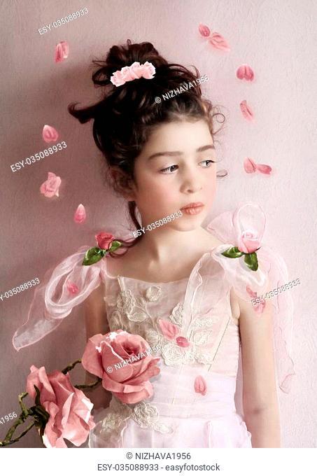 Little girl in a beautiful dress in rose petals