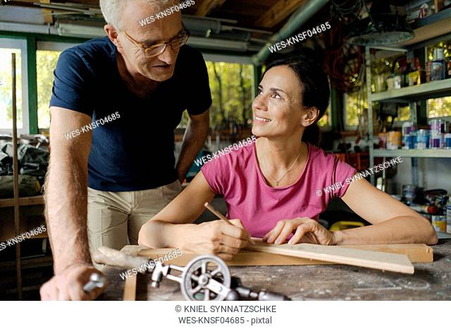 Smiling mature man watching woman working in workshop