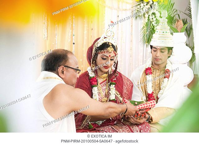 Couple performing religious ceremony in Bengali wedding