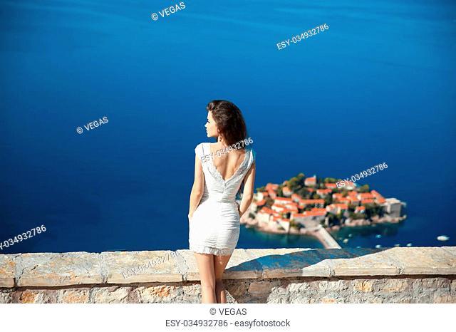 Beautiful brunette over blue sky posing in white dress. holidays, vacation, travel. Sveti Stefan island in Budva. Montenegro