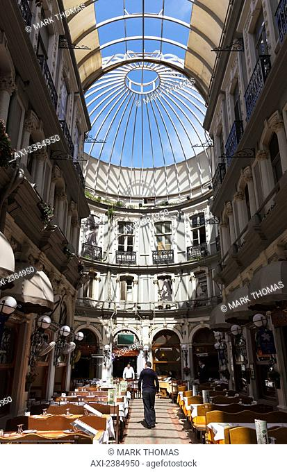 Tables and chairs inside the corridor of a building with a glass dome ceiling; Istanbul, Turkey