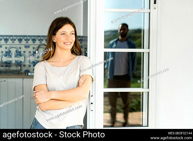 Smiling young woman leaning onto door looking at her boyfriend standing outside