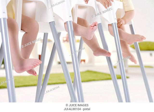 Three babies sitting in high chairs