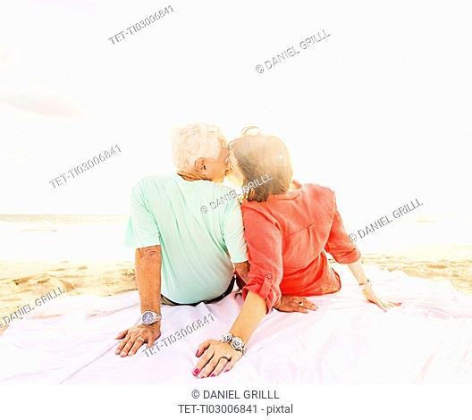 Rear view of couple kissing on beach at sunrise