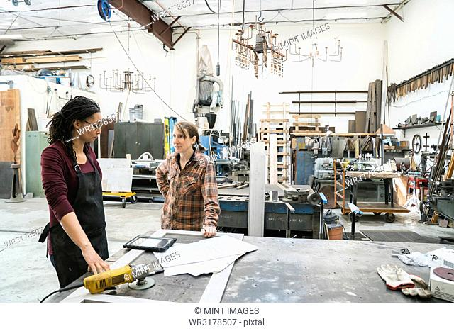 Two women standing at workbench in metal workshop