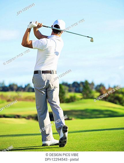 Man Playing Golf on Beautiful Sunny Green Golf Course. Hitting Golf Ball down the Fairway