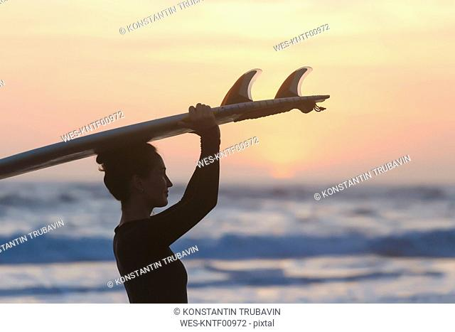 Indonesia, Bali, young woman with surfboard carrying on head at sunset