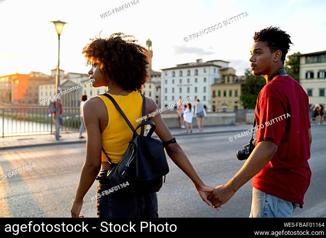 Young tourist couple exploring the city at sunset, Florence, Italy