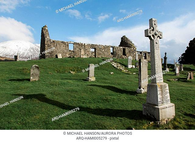 Cemetery gravestones and ruin of old church on grassy hill, Scotland, UK