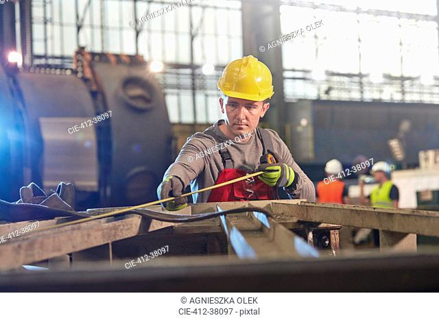 Male worker with tape measure measuring steel in factory