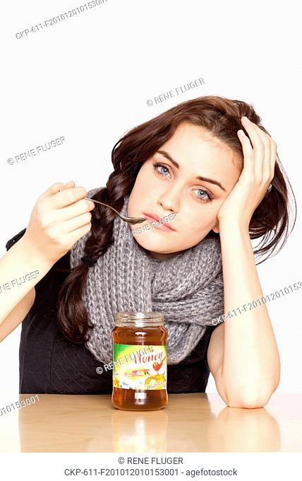 A beautiful young woman, lady, girl, cold, runny nose, headache, tea, honey, spoon, scarf