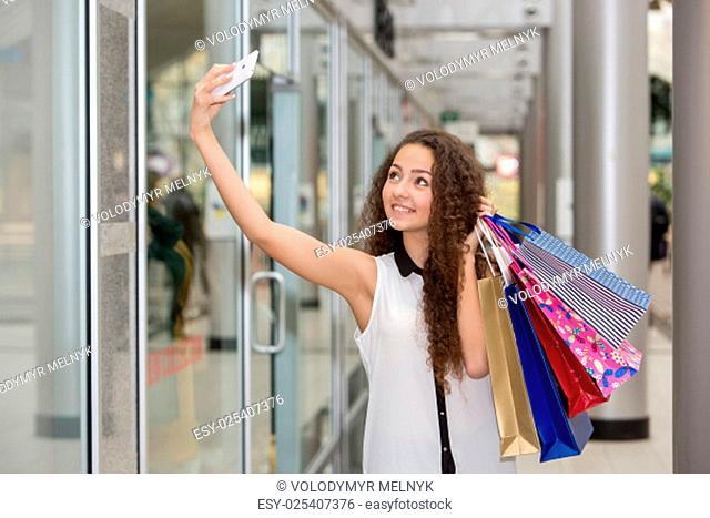 beautiful young woman goes shopping using a smartphone with a shopping bags in the mall