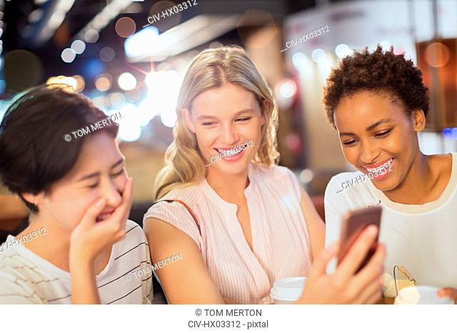 Laughing young friends with cell phone at cafe