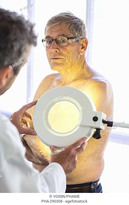 Doctor examining the skin of a man