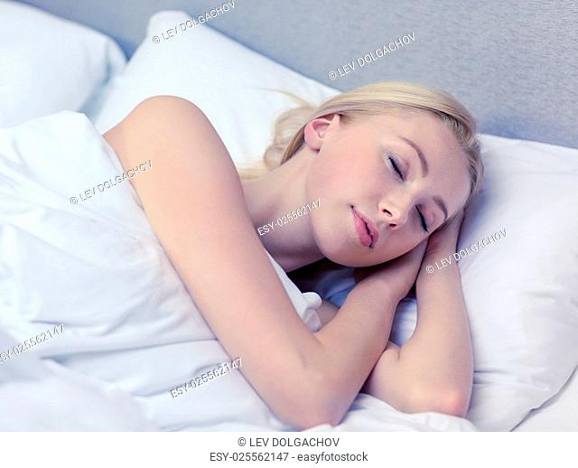 hotel, travel and happiness concept - beautiful woman sleeping in bed